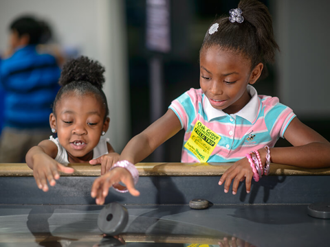 Two young girls enjoy the spinee table in the Aerospace Exhibit