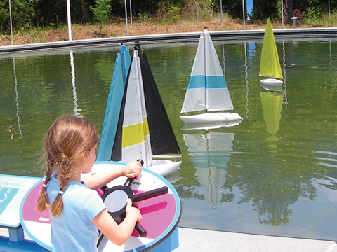 A girl plays with the sail boats on a sunny day