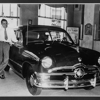 A salesman shows off a new Ford model in the showroom of a Hull-Dobbs dealership.