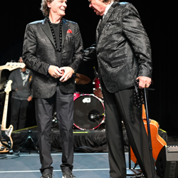 BJ Thomas and Mark James share a laugh on stage.