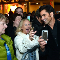 Elvis fan and actor John Stamos snaps photos with fans before the Lighting Ceremony.
