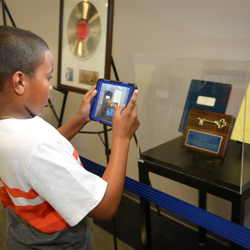 This little Elvis snaps a photos of artifacts on display inside the new Graceland Archive Studio.