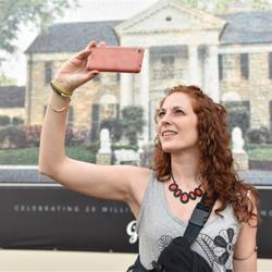 Fans snap selfies in front of the new Graceland fan mosaic.