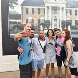 Fans snap a selfie in front of the new Graceland fan mosaic.