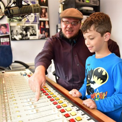 DJ Argo teaches a student about how the controls work at the Sirius XM Elvis Radio booth.