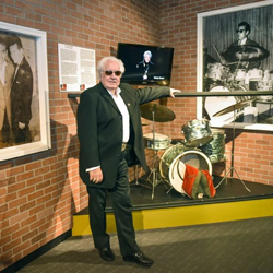"W.S. Holland, who played drums for Carl Perkins and Johnny Cash, stands near his drum set in the ""Hillbilly Rock"" exhibit."