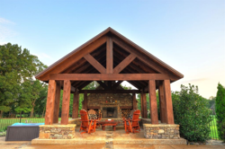 Rough cedar cabana structure with decorative accent beam, a metal roof, and a stacked stone fireplace