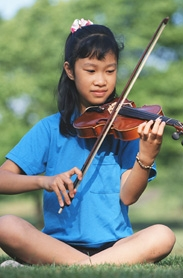 A young girl playing her violin outside