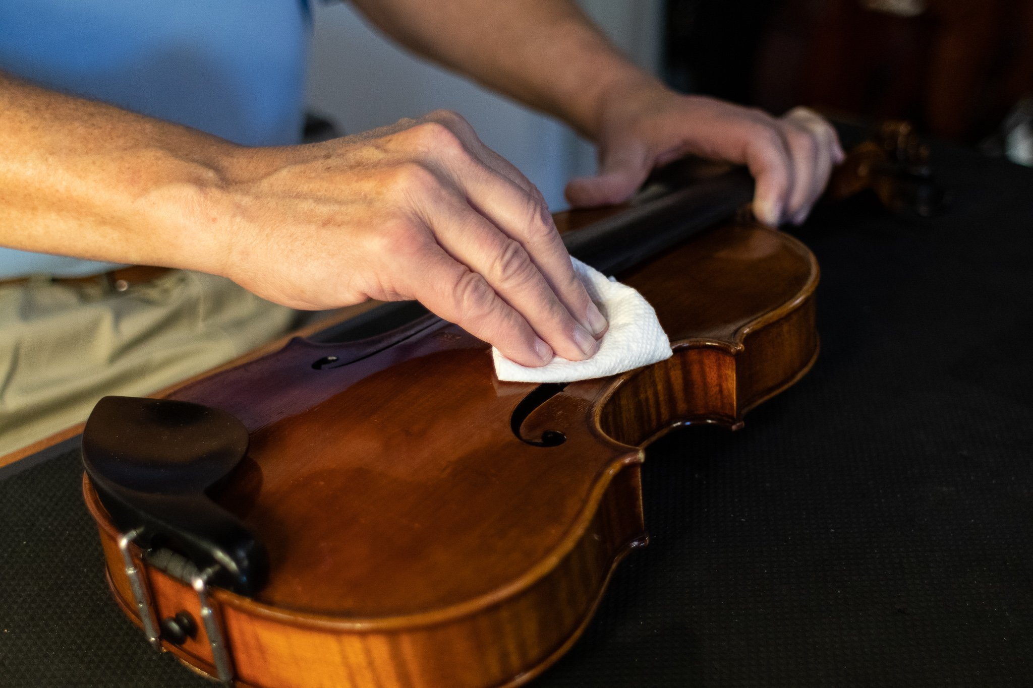 A string technician polishes a violin