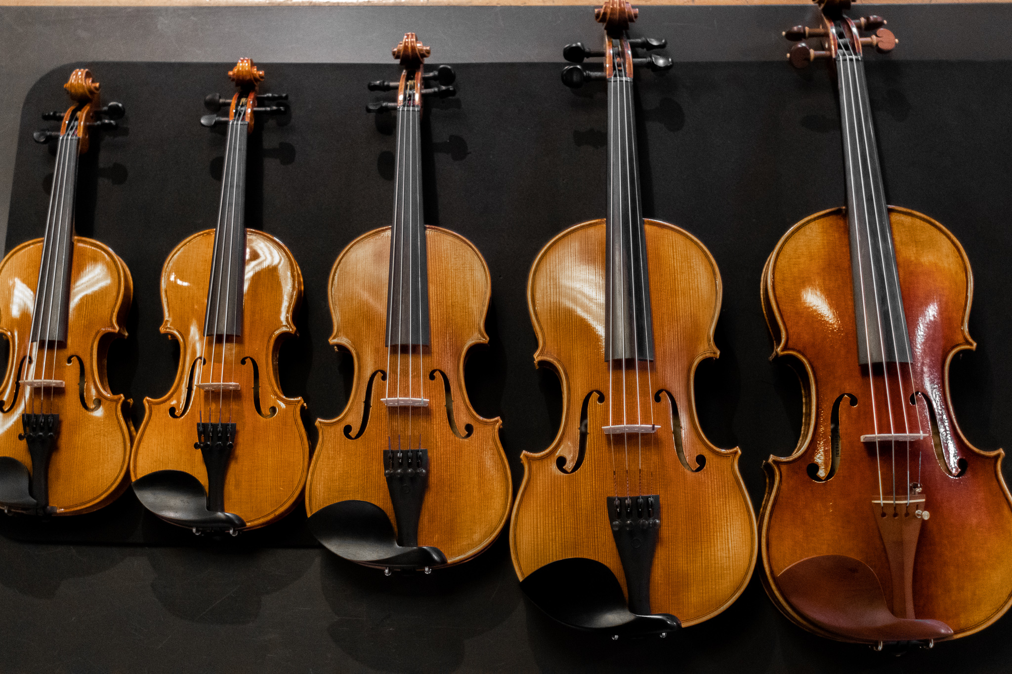 a photo comparing the different fractional sizes of violins that Amro carries