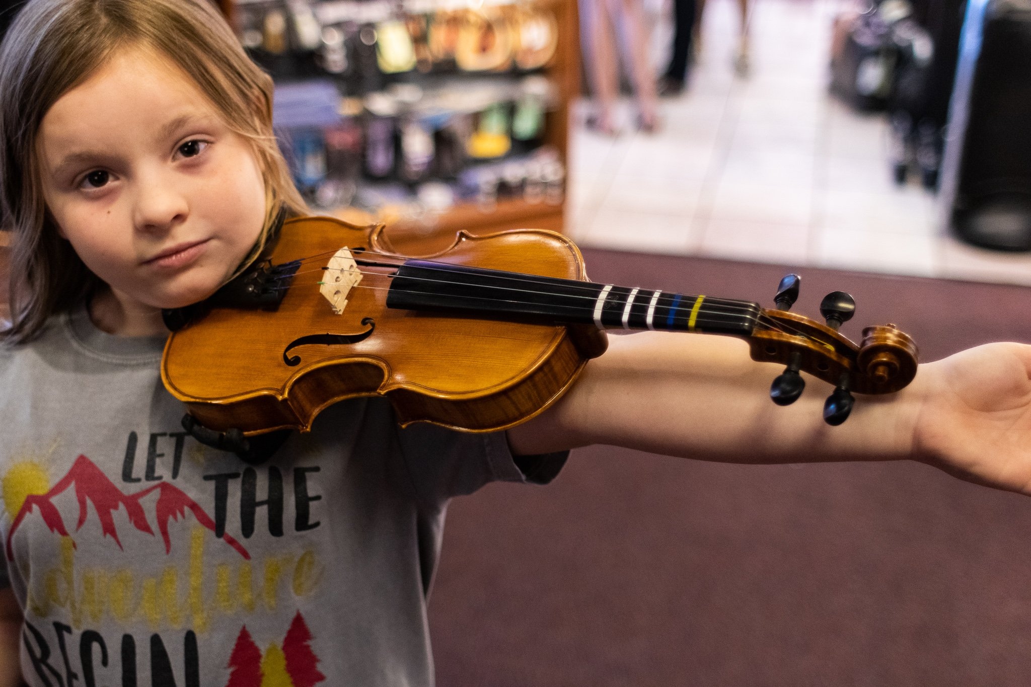 A young violinist is being checked to see if she should move up to the next size