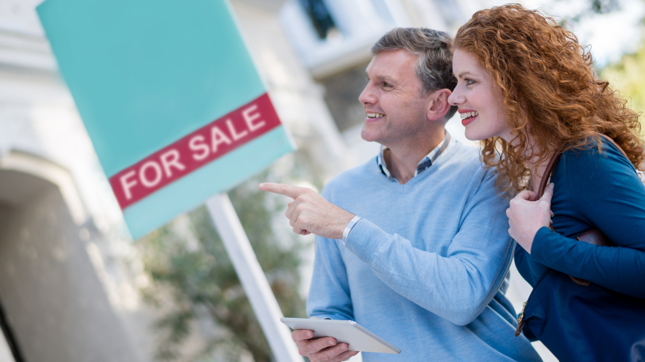 couple looking at a for sale sign
