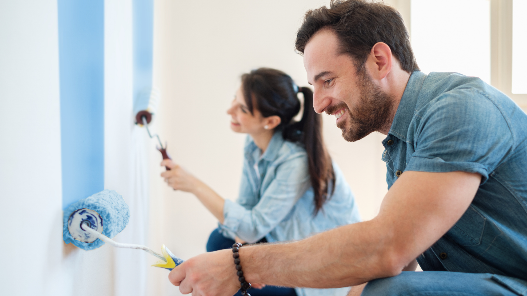 couple painting a wall blue
