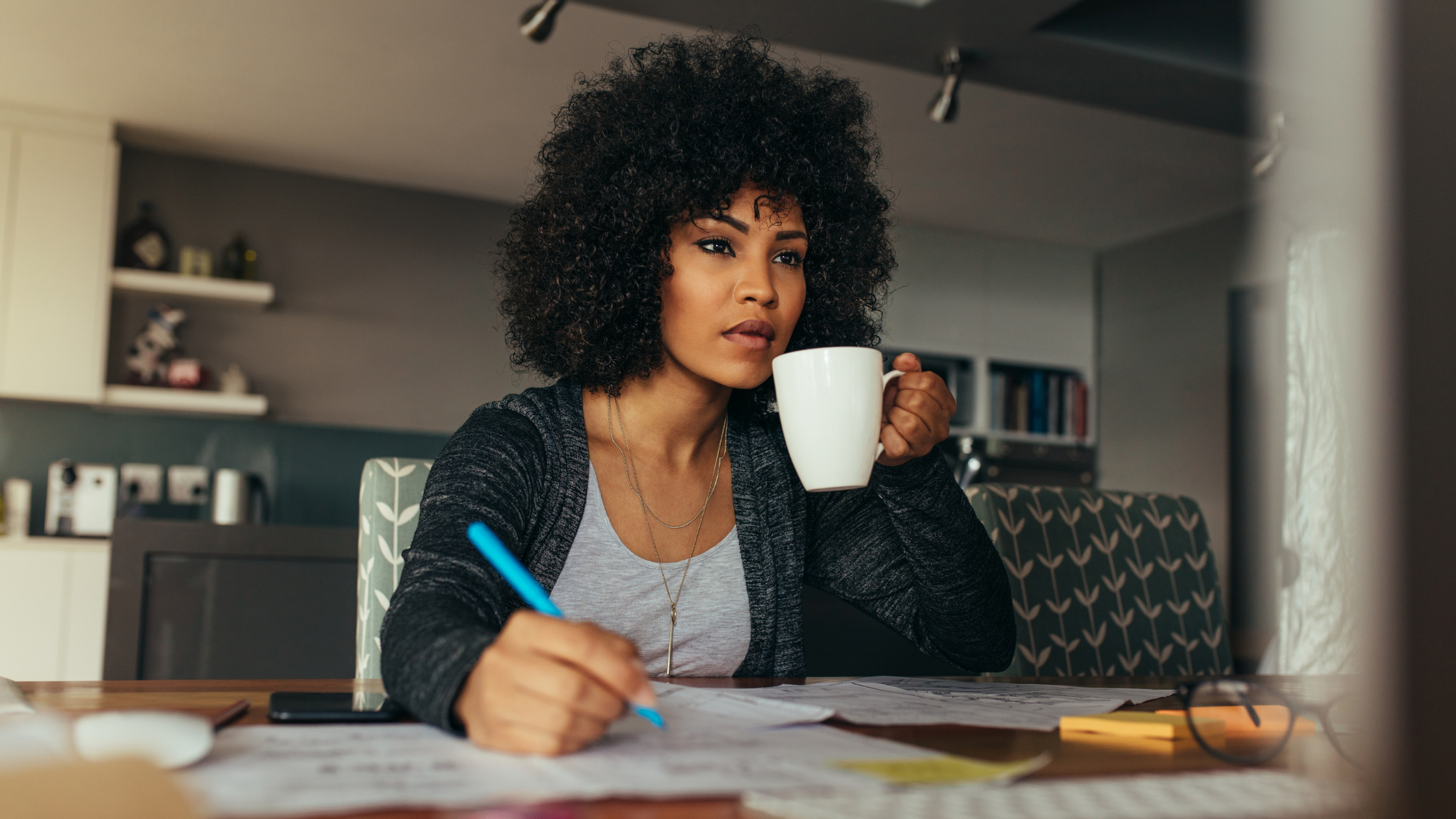 woman drinking from a mug in home office