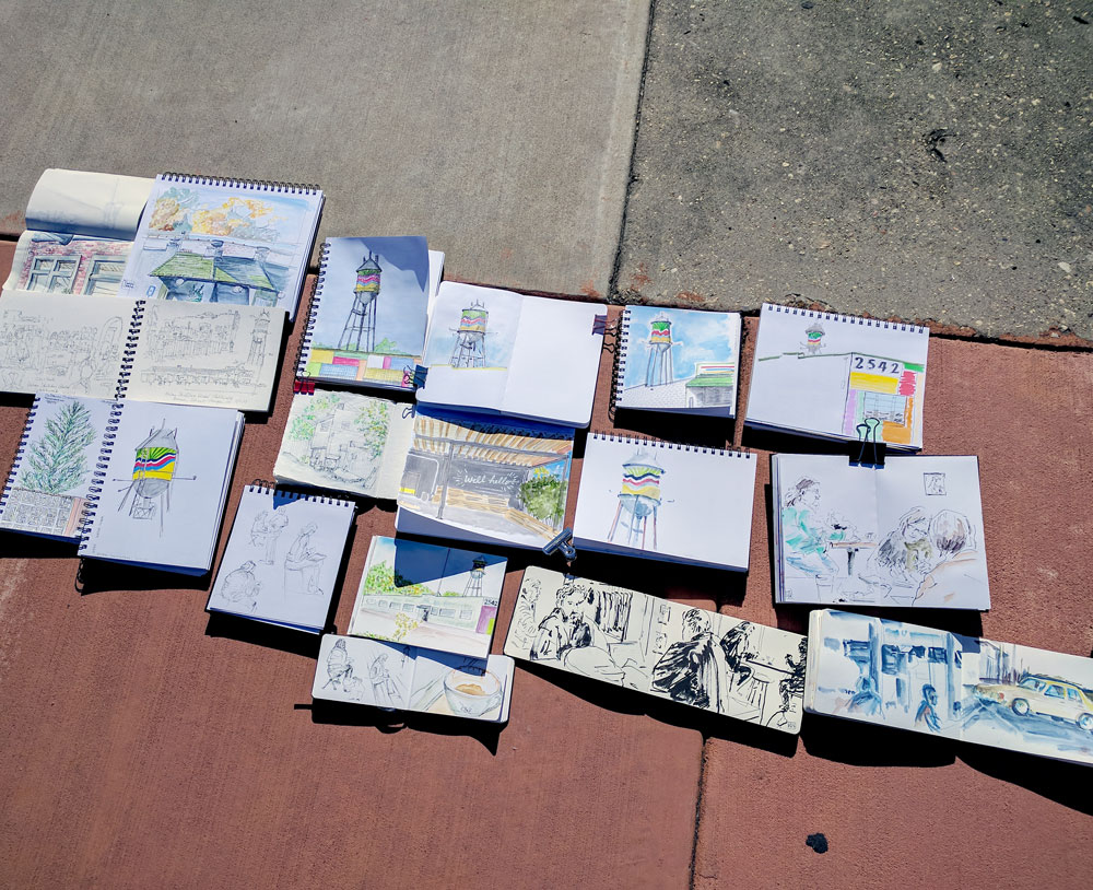 several open sketchbooks laying on a sidewalk, photo from above