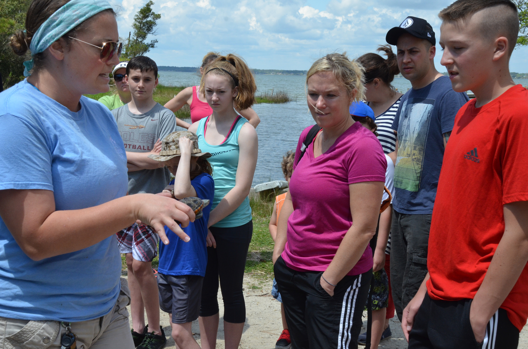 Volunteers learn about natural habitats and local animals before planting marsh grass.