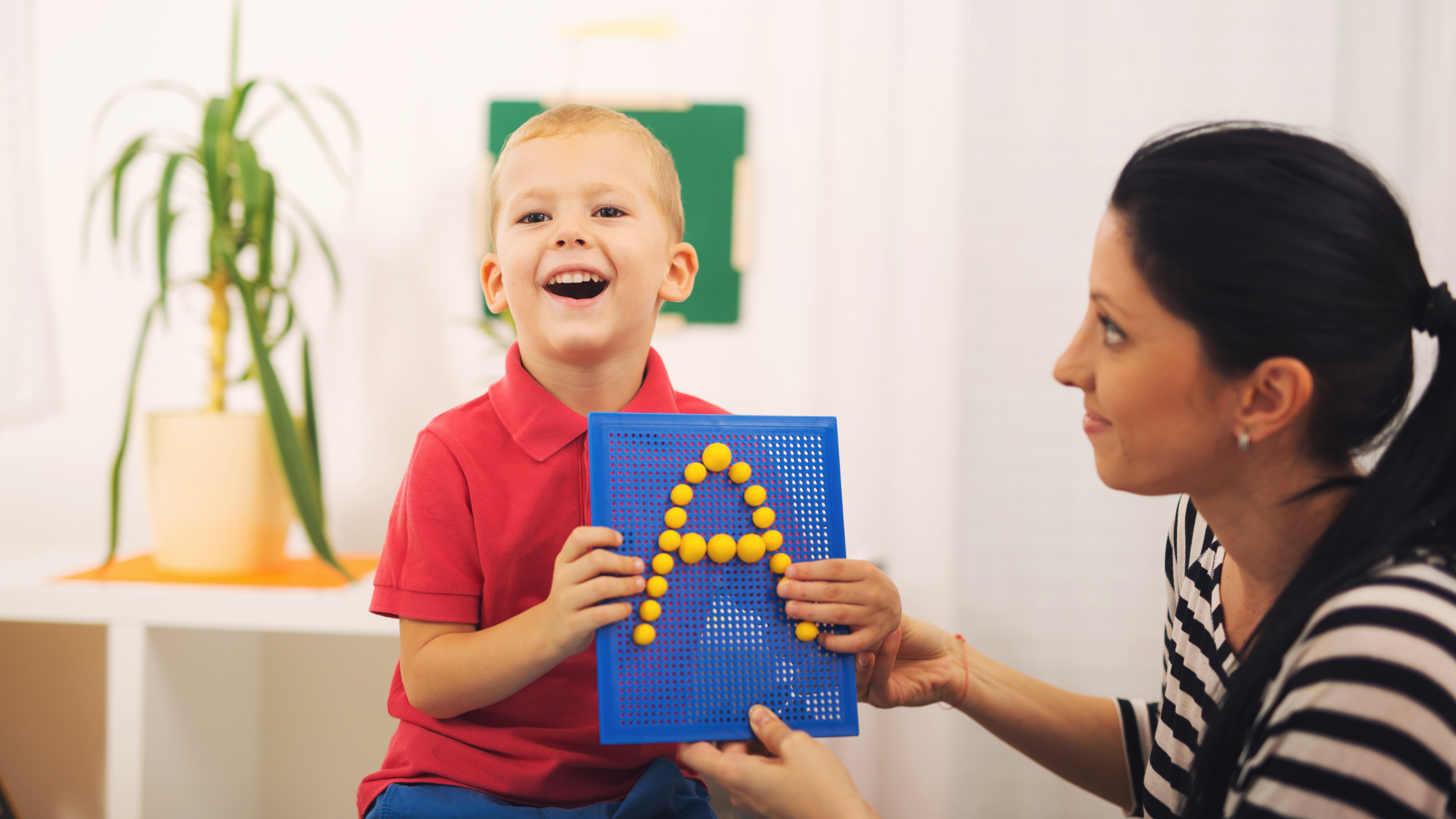 little boy holding up the letter A with help from a teacher