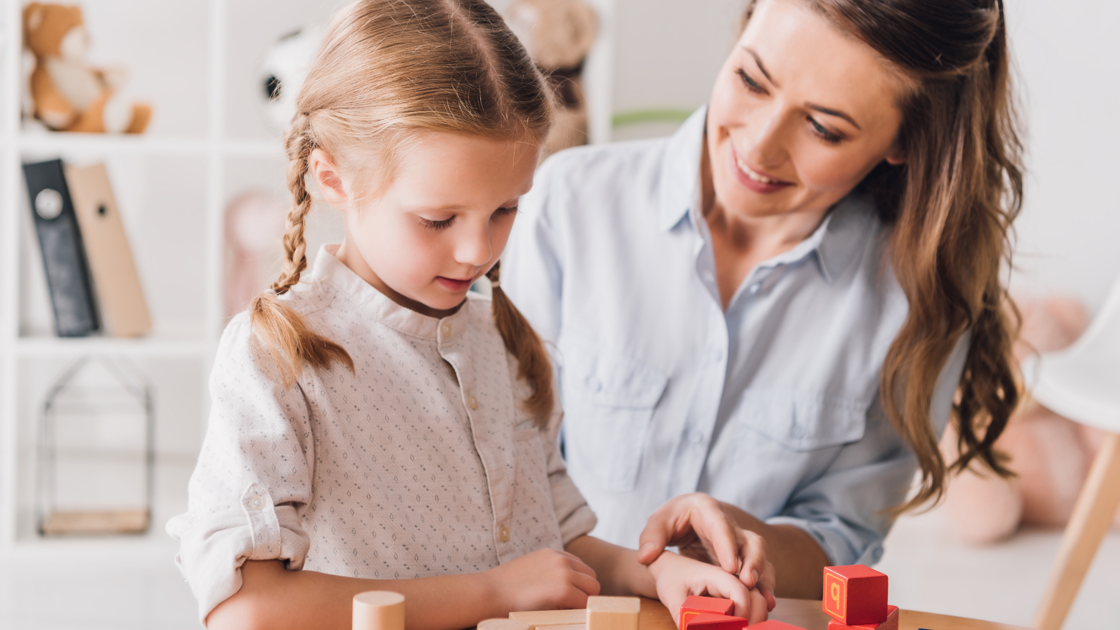 little girl playing with blocks with a teacher