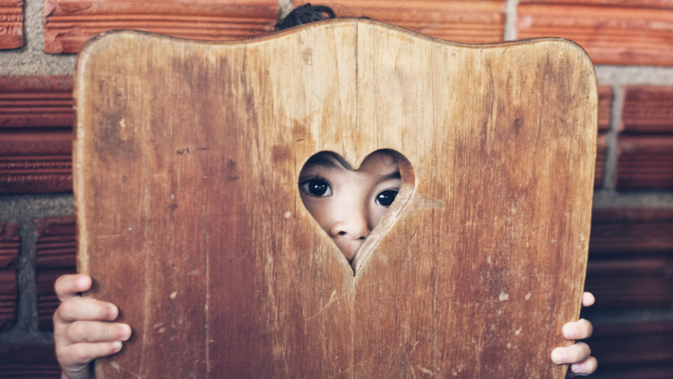 child peeking through the back of a chair through heart-shaped hole