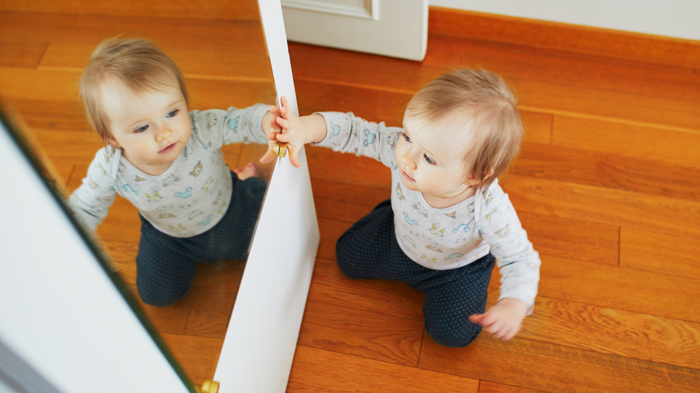 baby touching a mirror