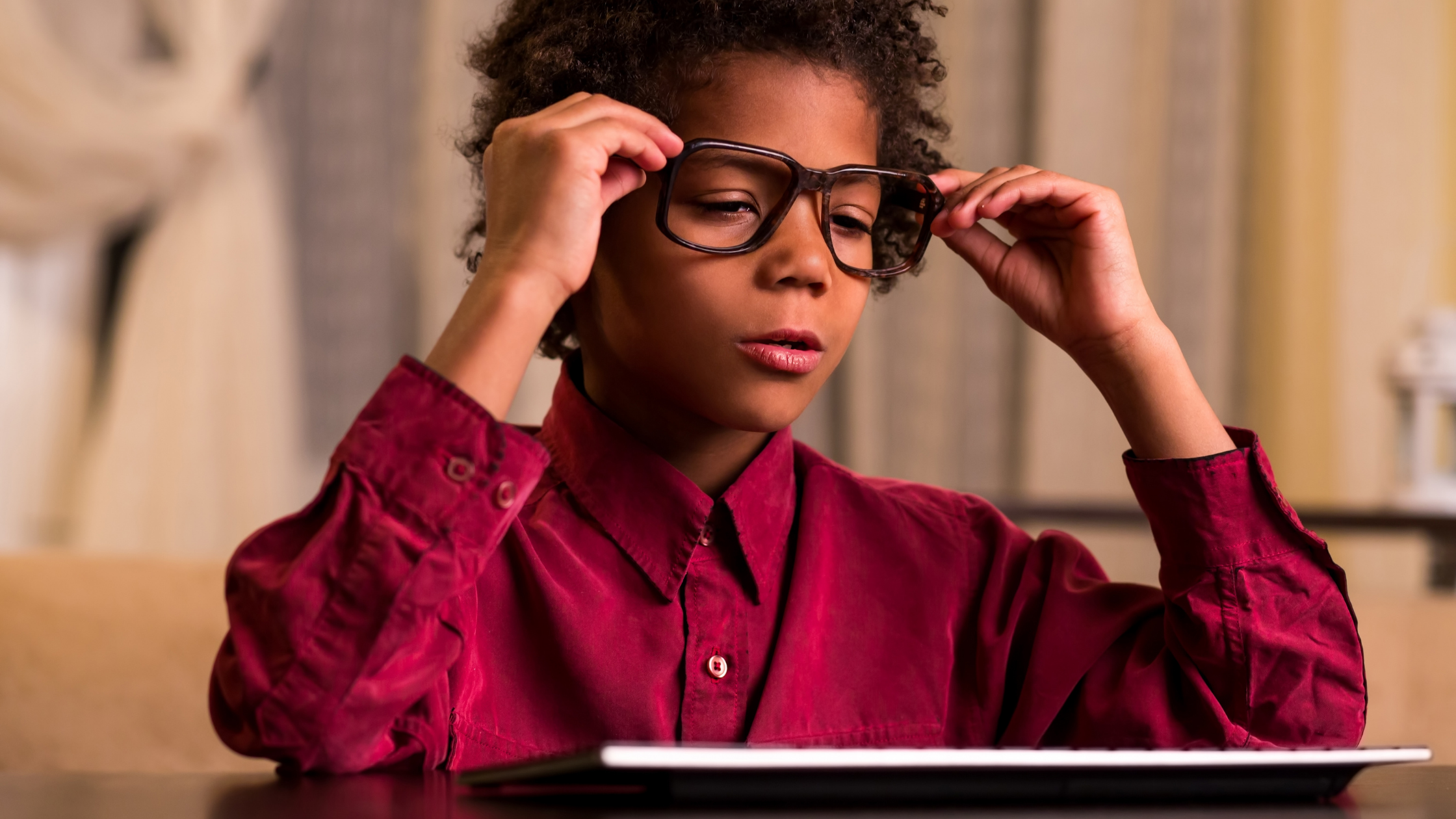 child with glasses looking at smart tablet