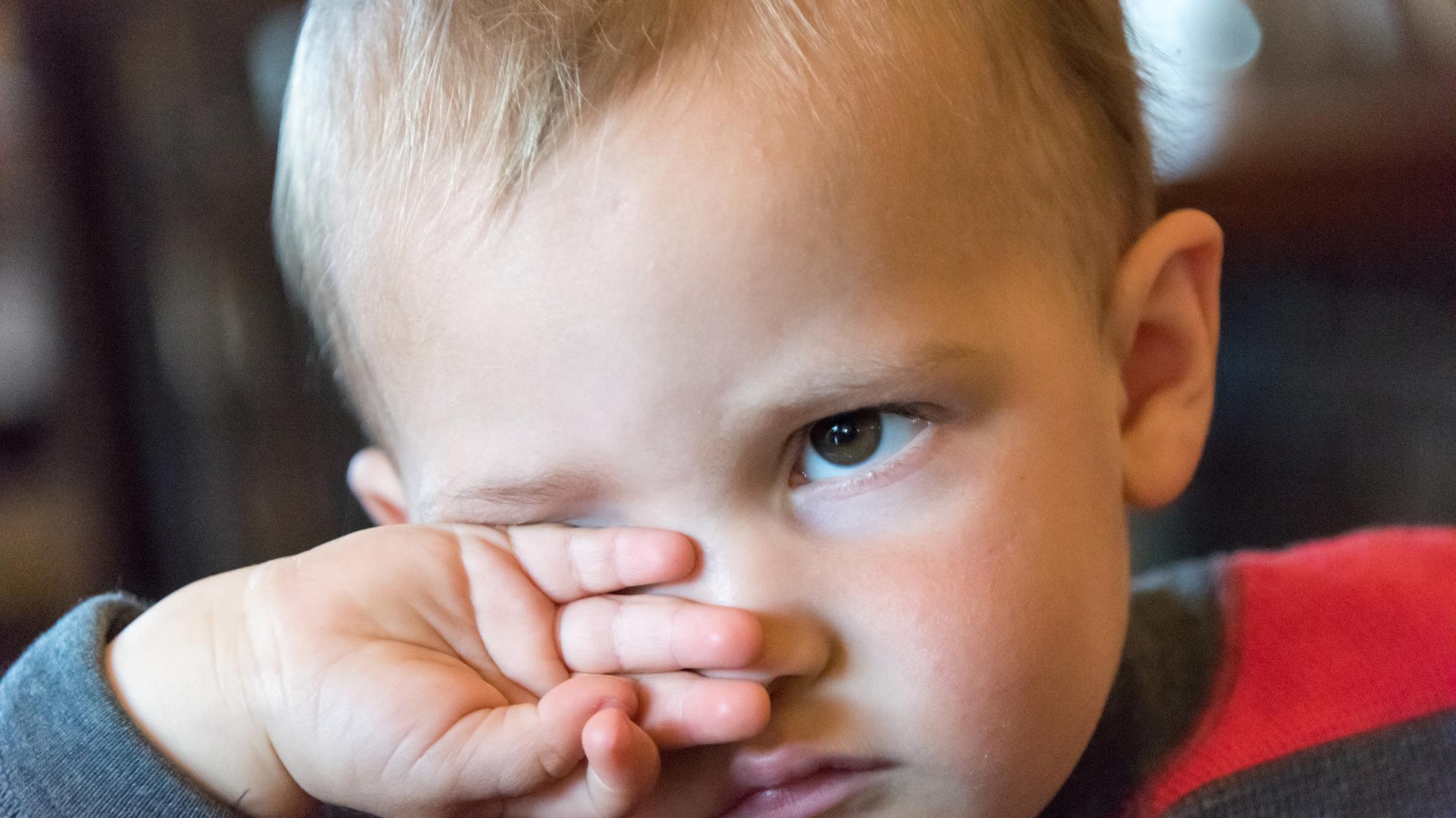 little boy rubbing his eyes