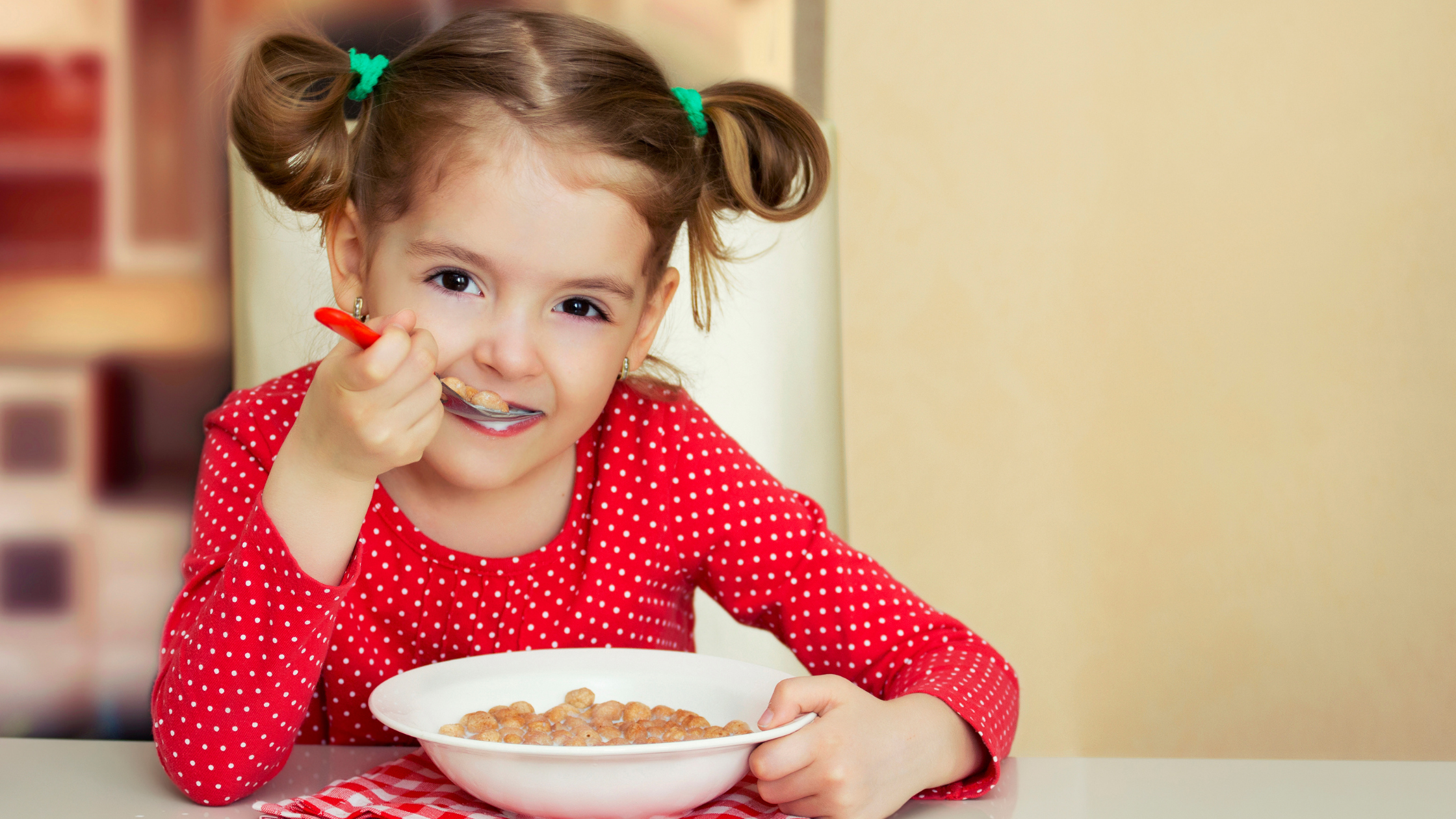 little girl with pigtails eating cereal