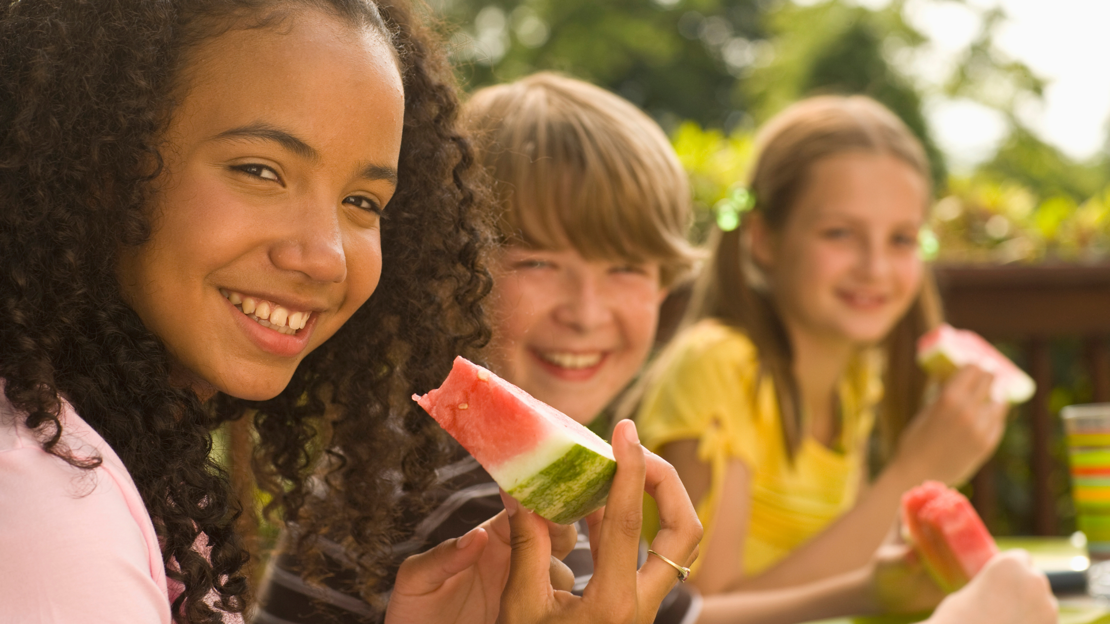 group of children eating watermelon