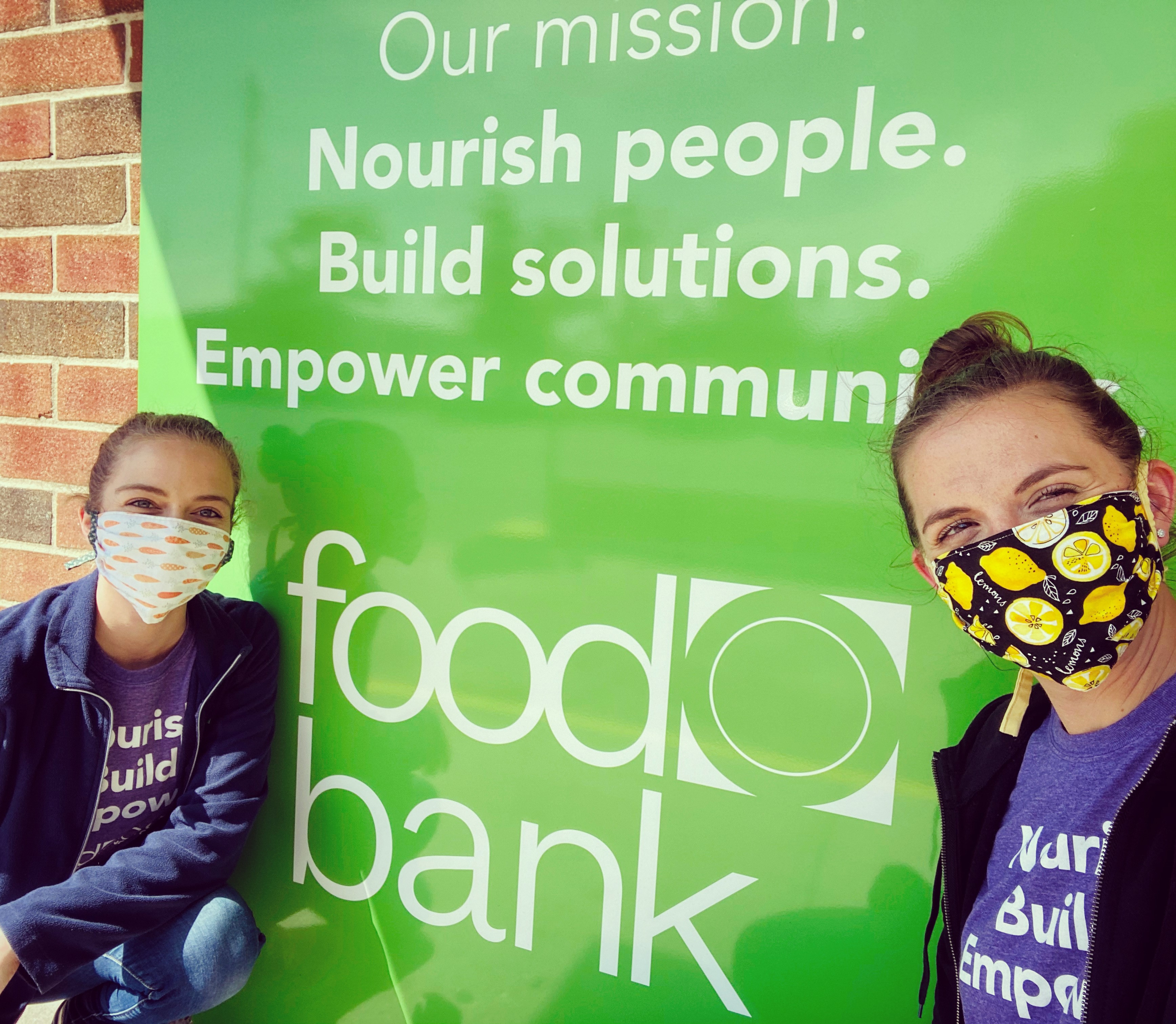 two women in masks working at a food bank