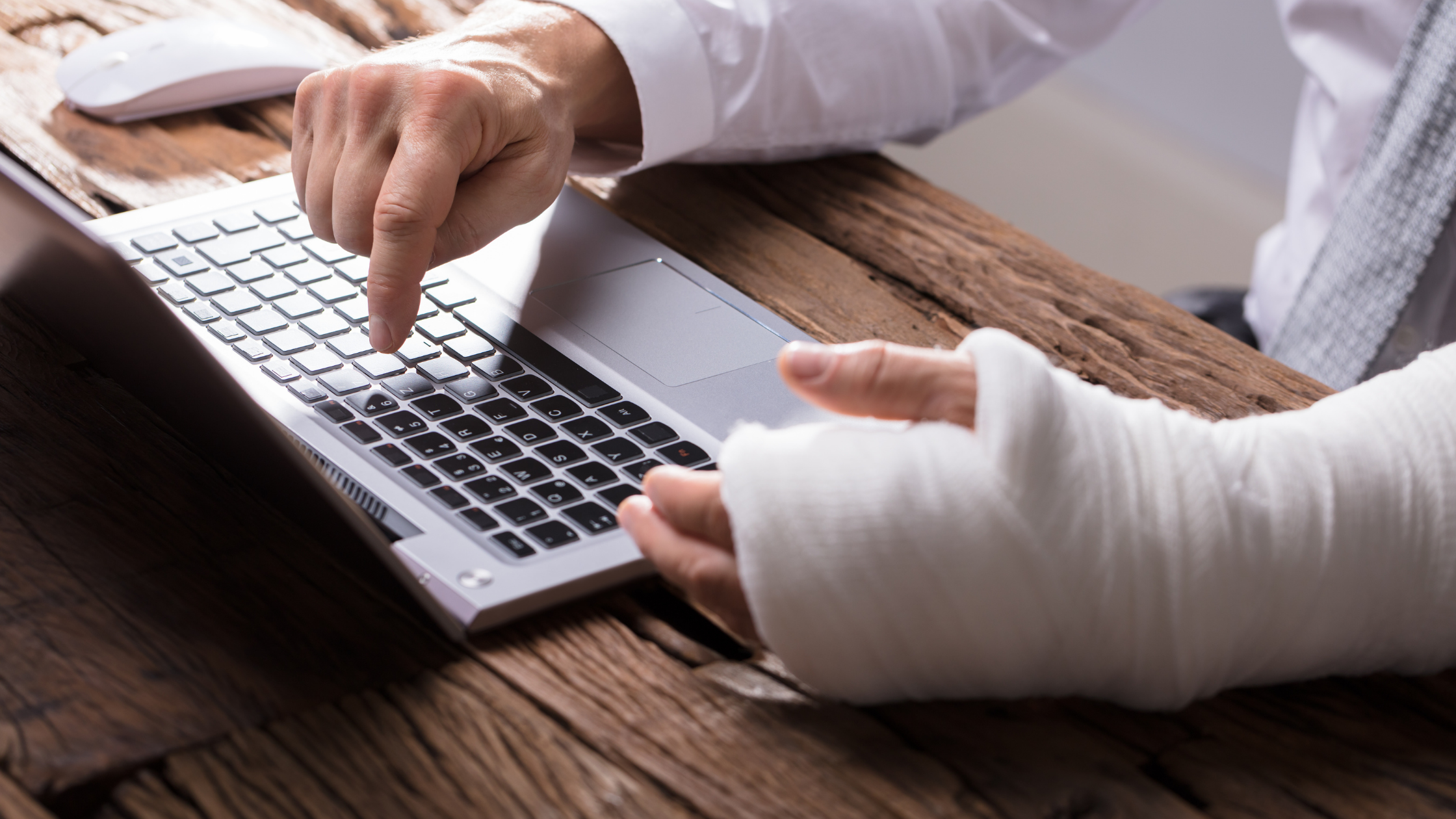 person typing with one finger and a cast