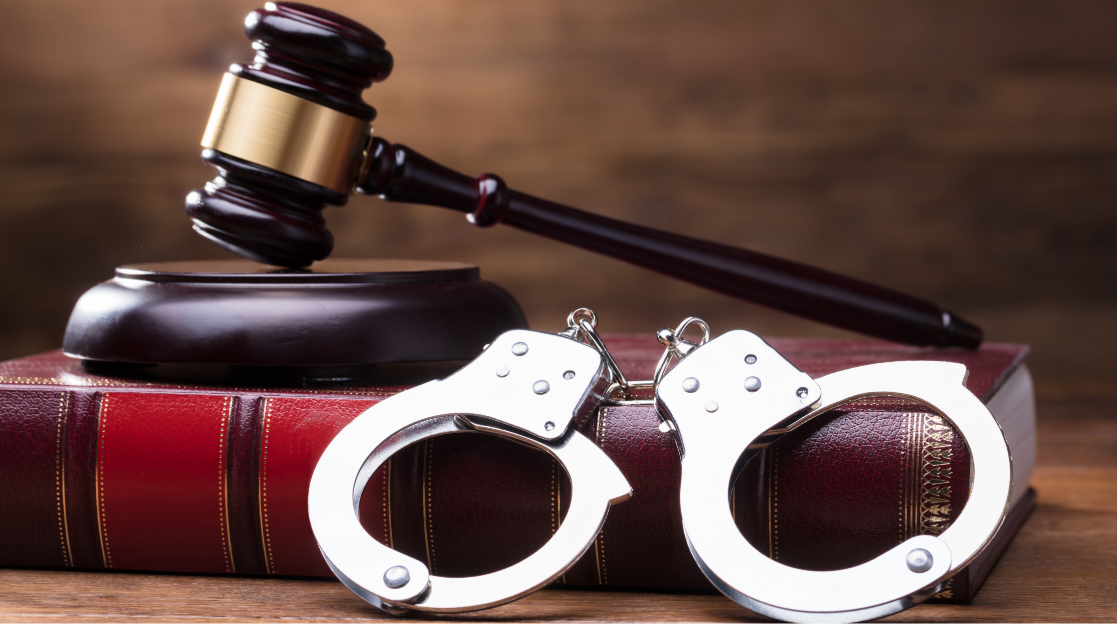 gavel with handcuffs and a law book