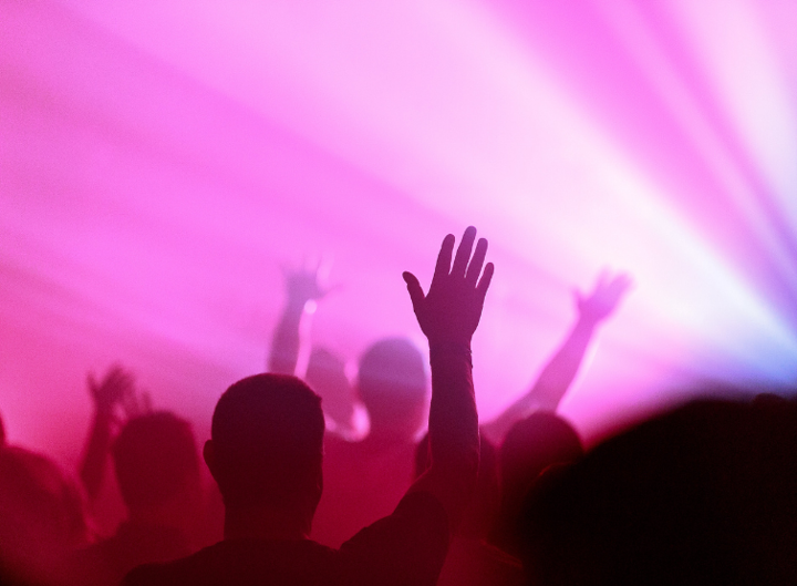 Man in worship service, in front of purple lights