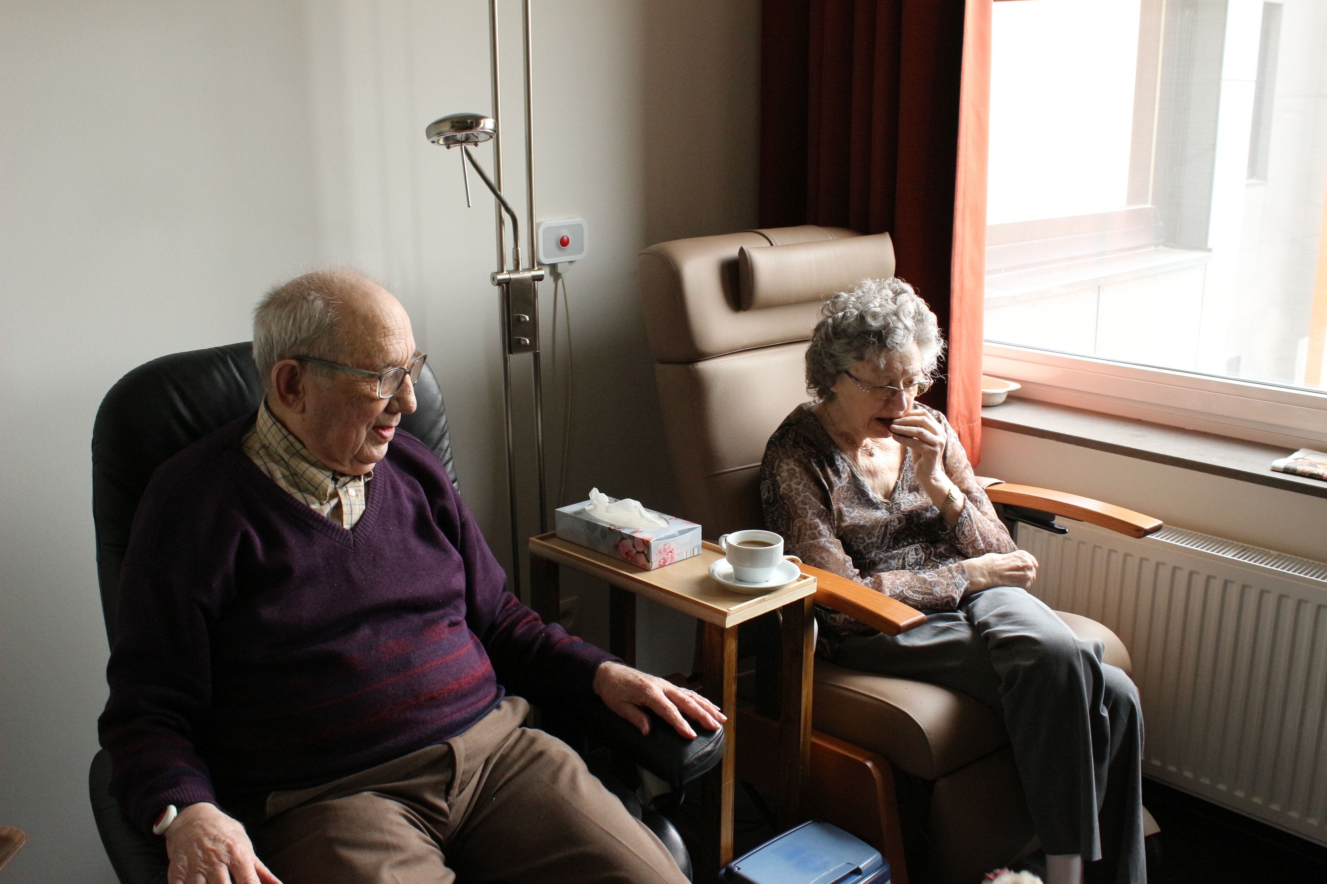 elderly man and woman sitting together reading