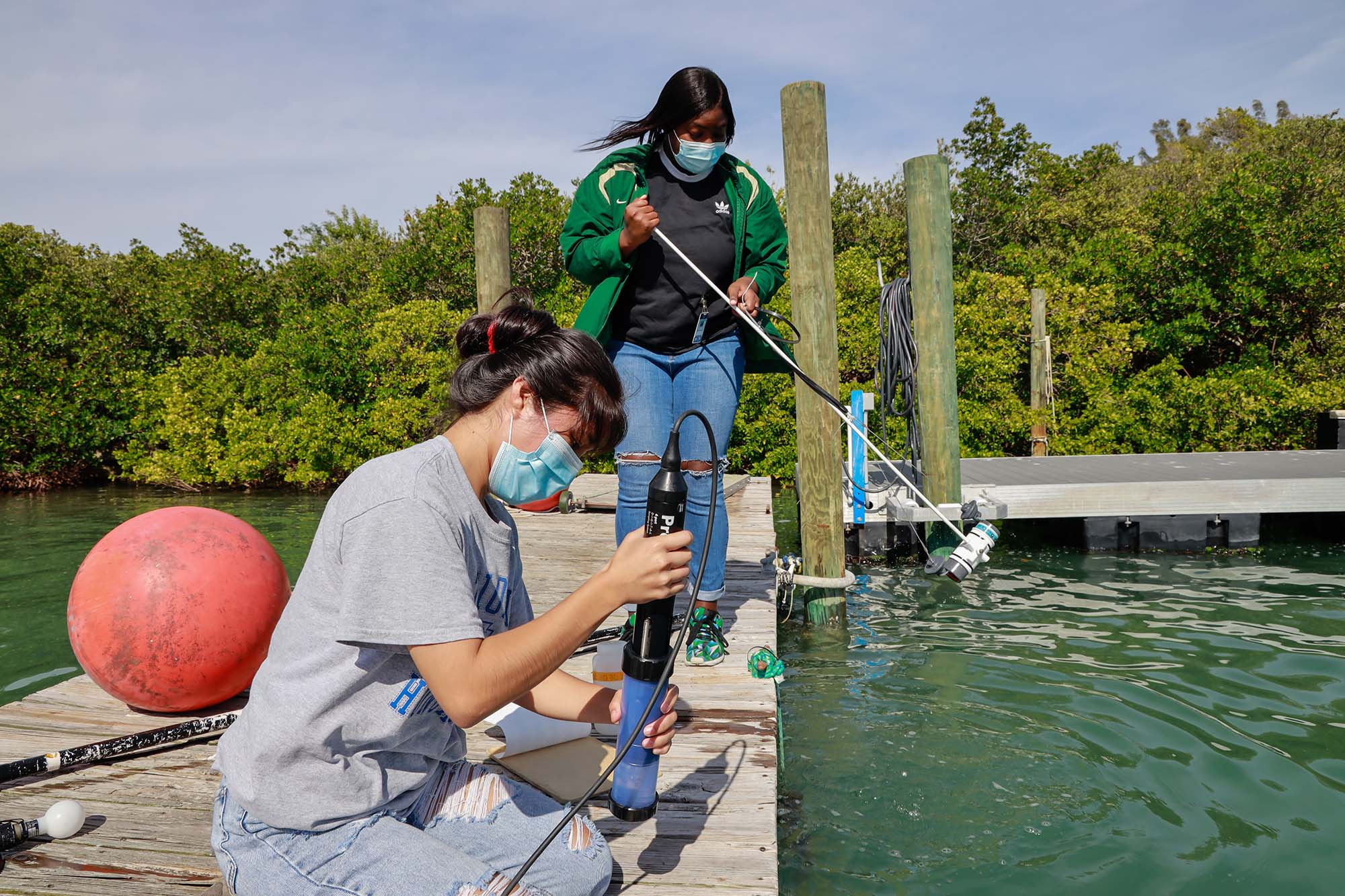 Mote staff, with help from an intern, collect water samples at Mote's dock and process them in Dr. Vincent Lovko's lab. Pictured (from left): MarSci-LACE intern Niky Roblero; Giandria Green, former MarSci-LACE intern and now Mote staff. Photo Credit - © Mote Marine Laboratory