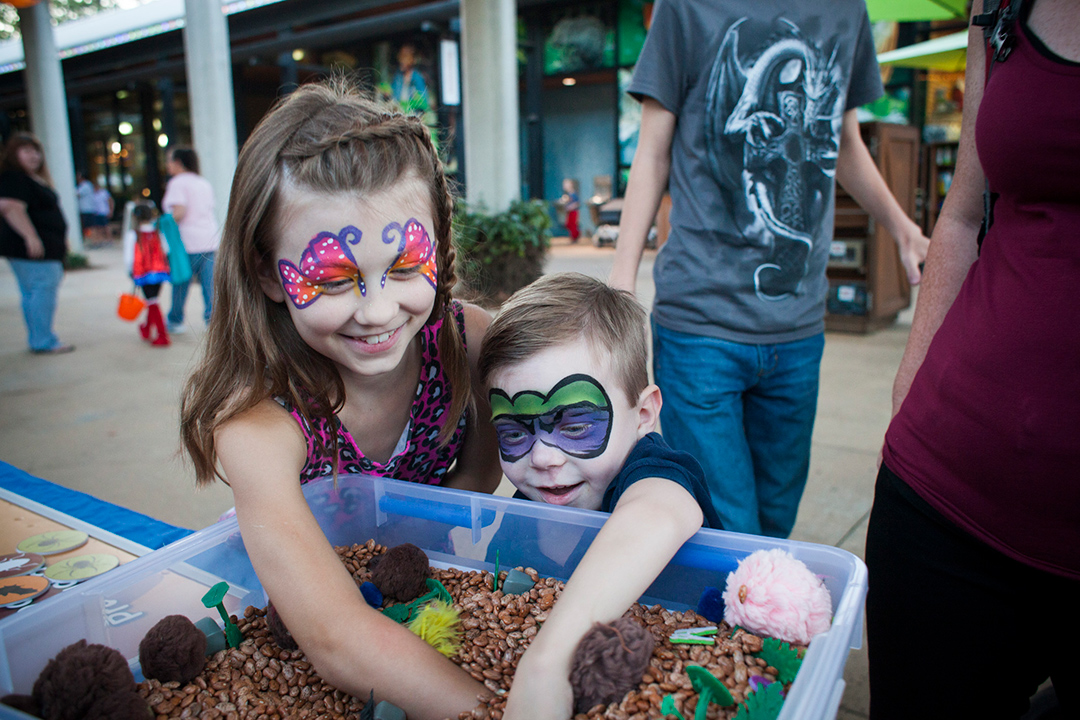 Two kids with their faces painted reach into a sensory box