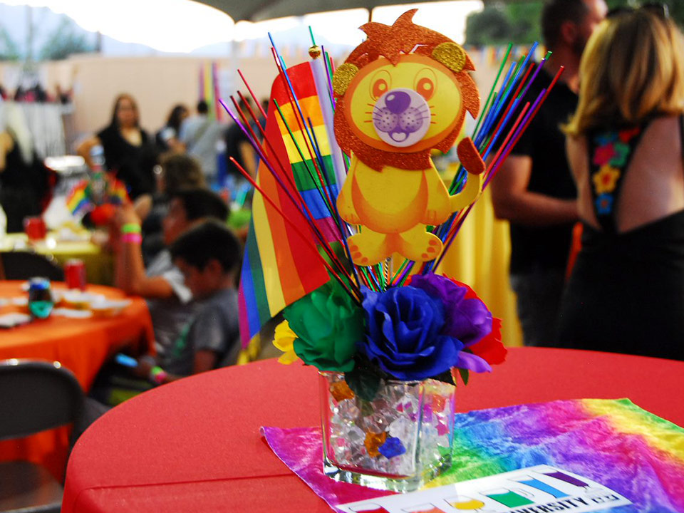 Photo of rainbow centerpiece with lion and flowers on table.