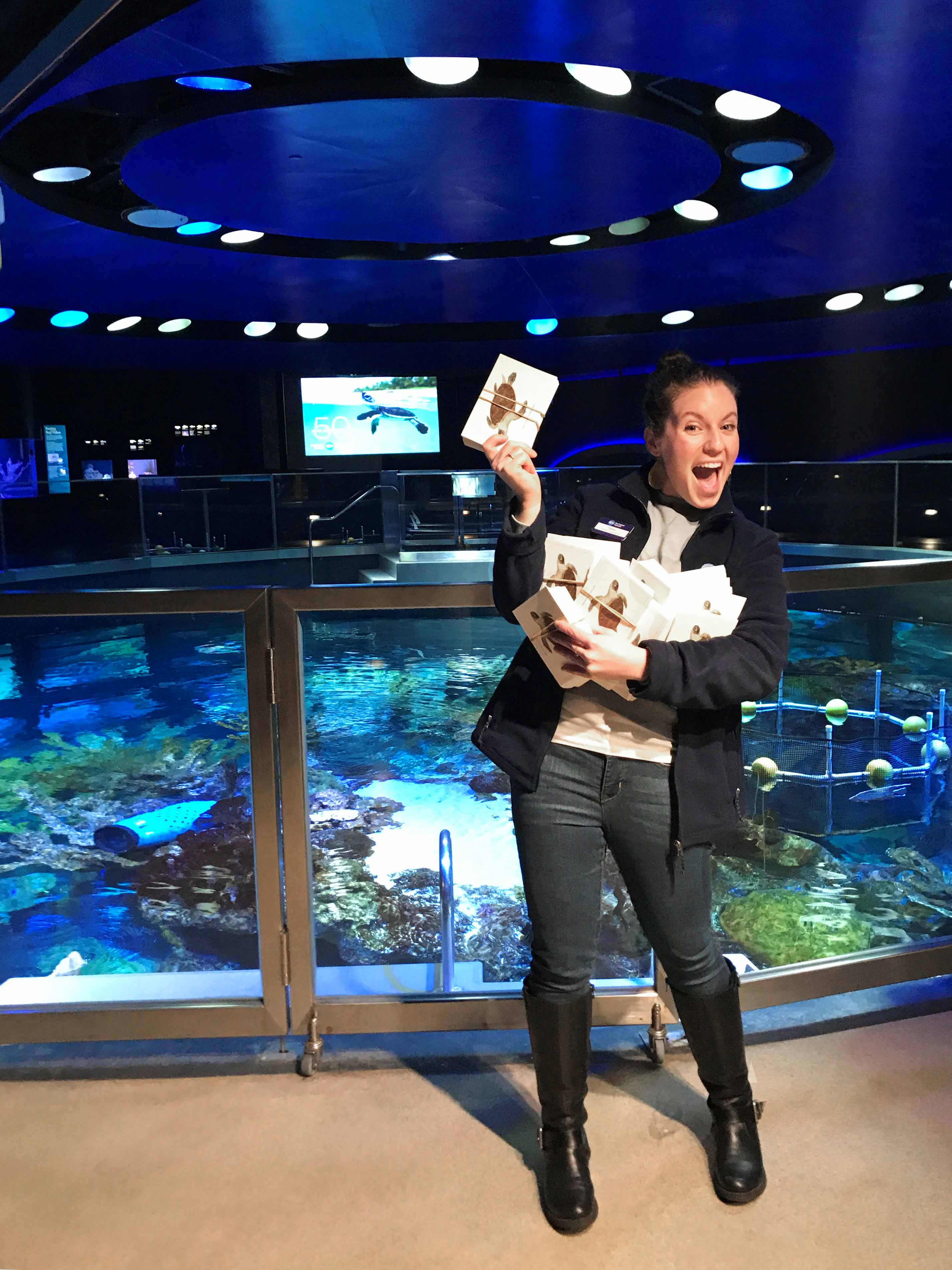Taylor Engelsman, content and evaluation specialist at the New England Aquarium, shows off signed postcards from visitors asking their elected officials to support 30x30.