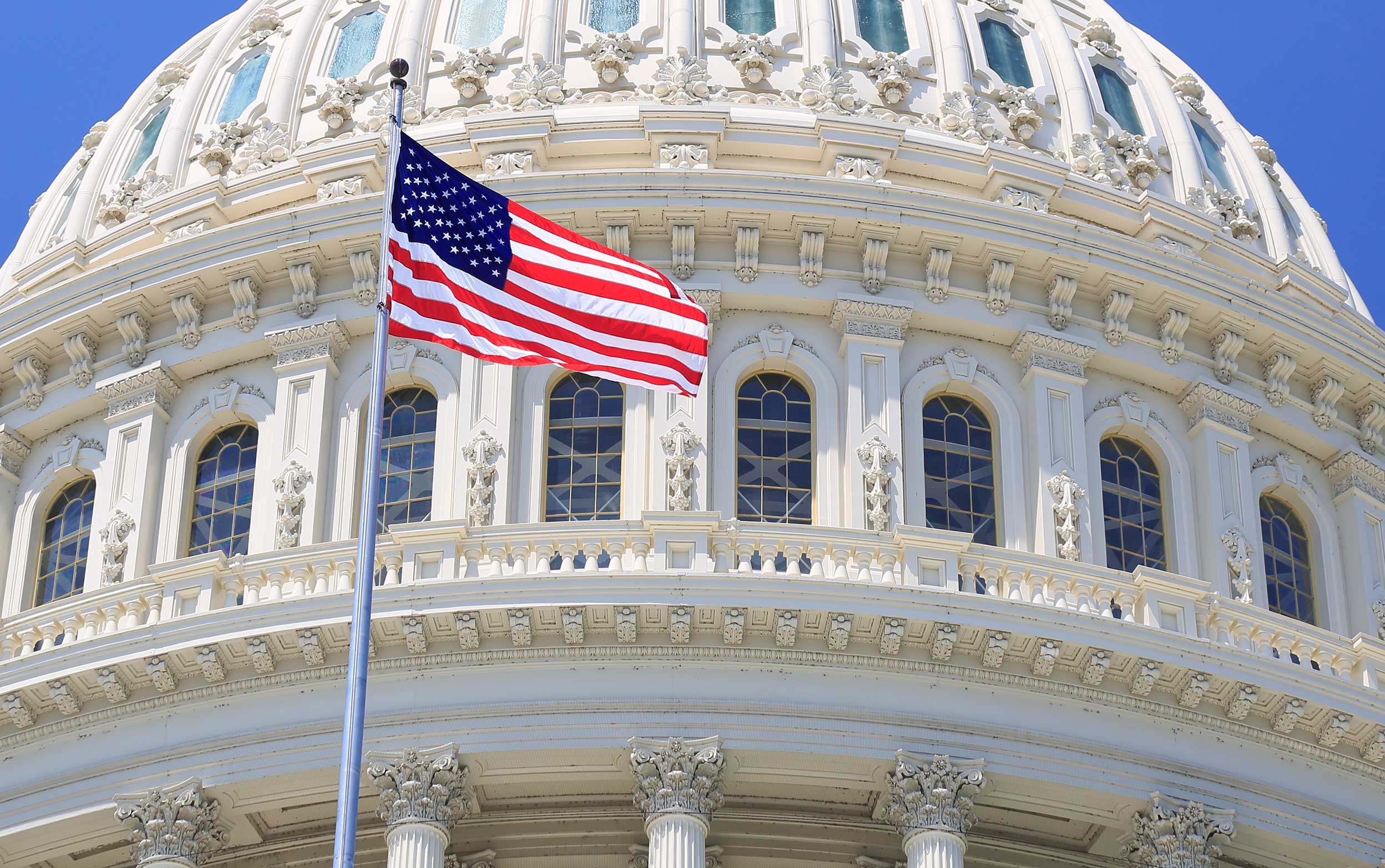 Flag waving in the air outside of the U.S. Capitol building