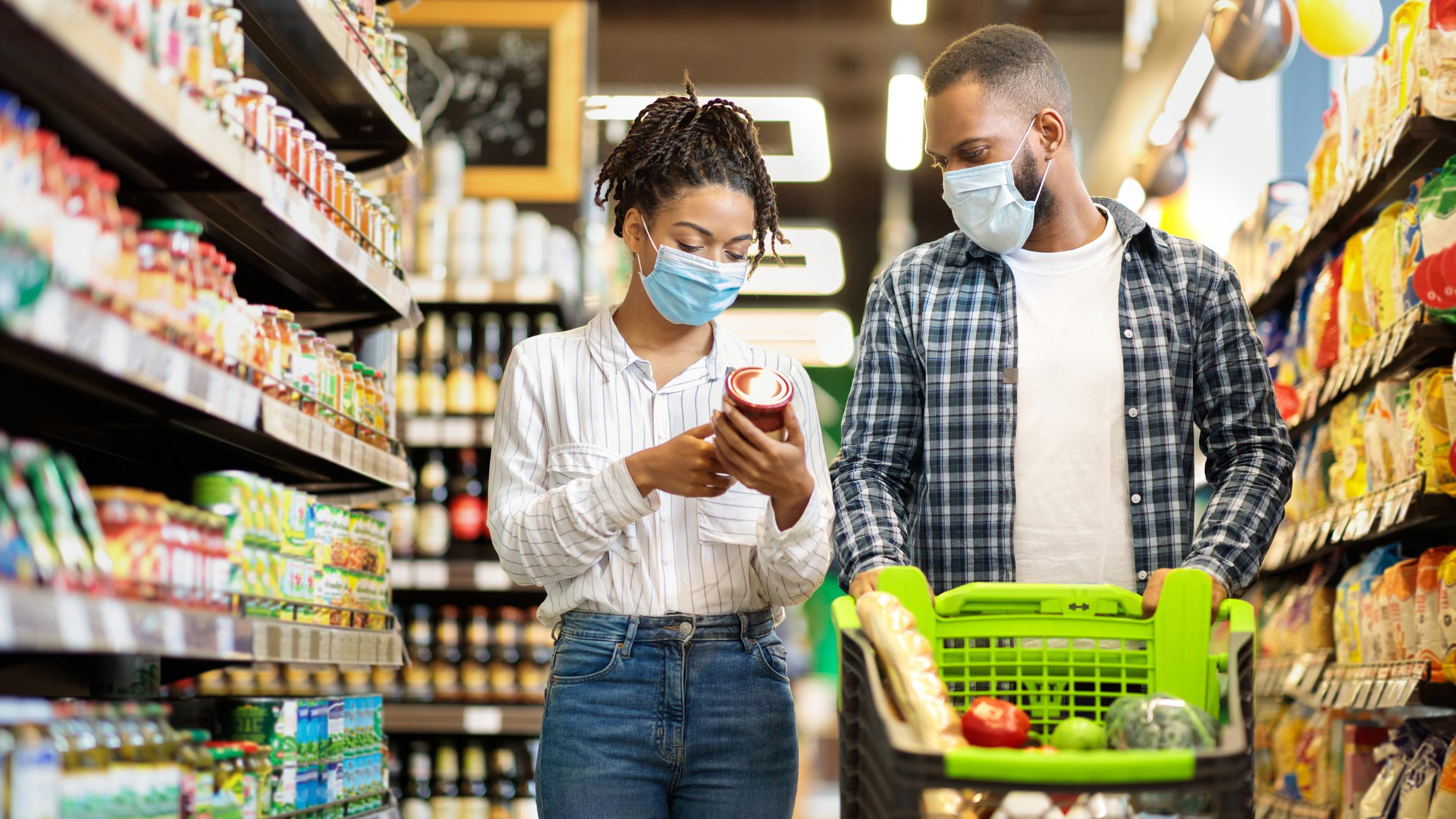 Two adults wearing masks and grocery shopping