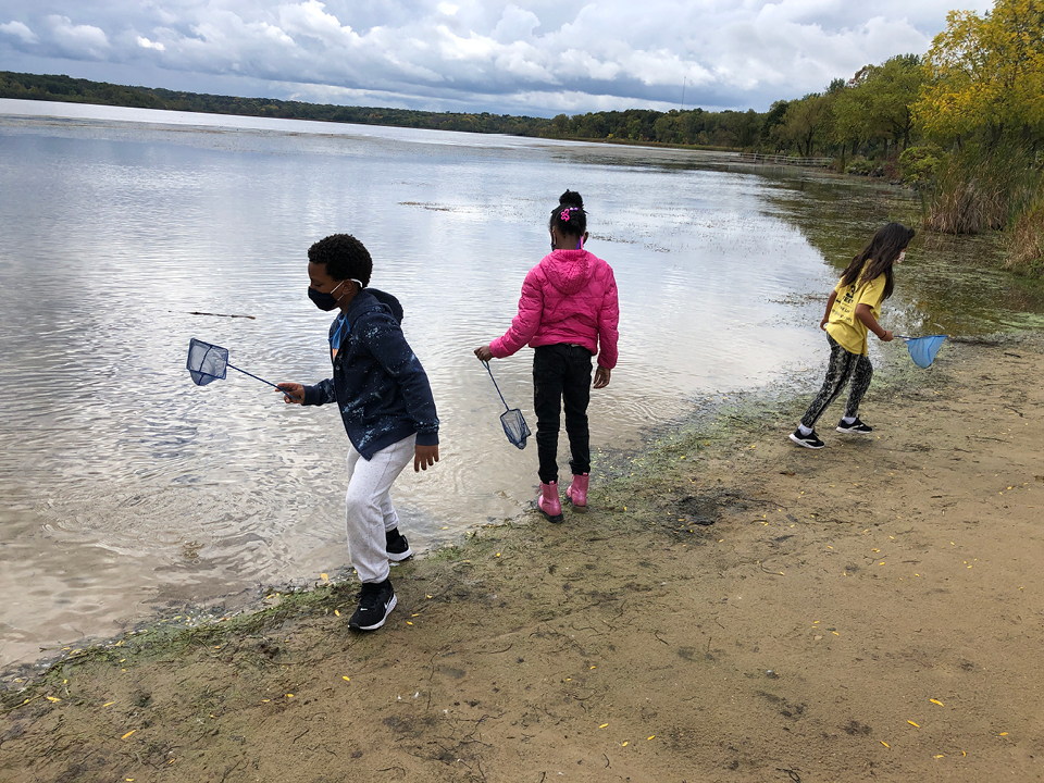 Three Zoo School students look for animals in a lake