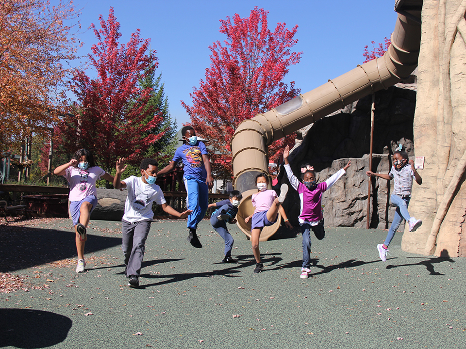 A group of young Zoo School students jump in the air at the playground