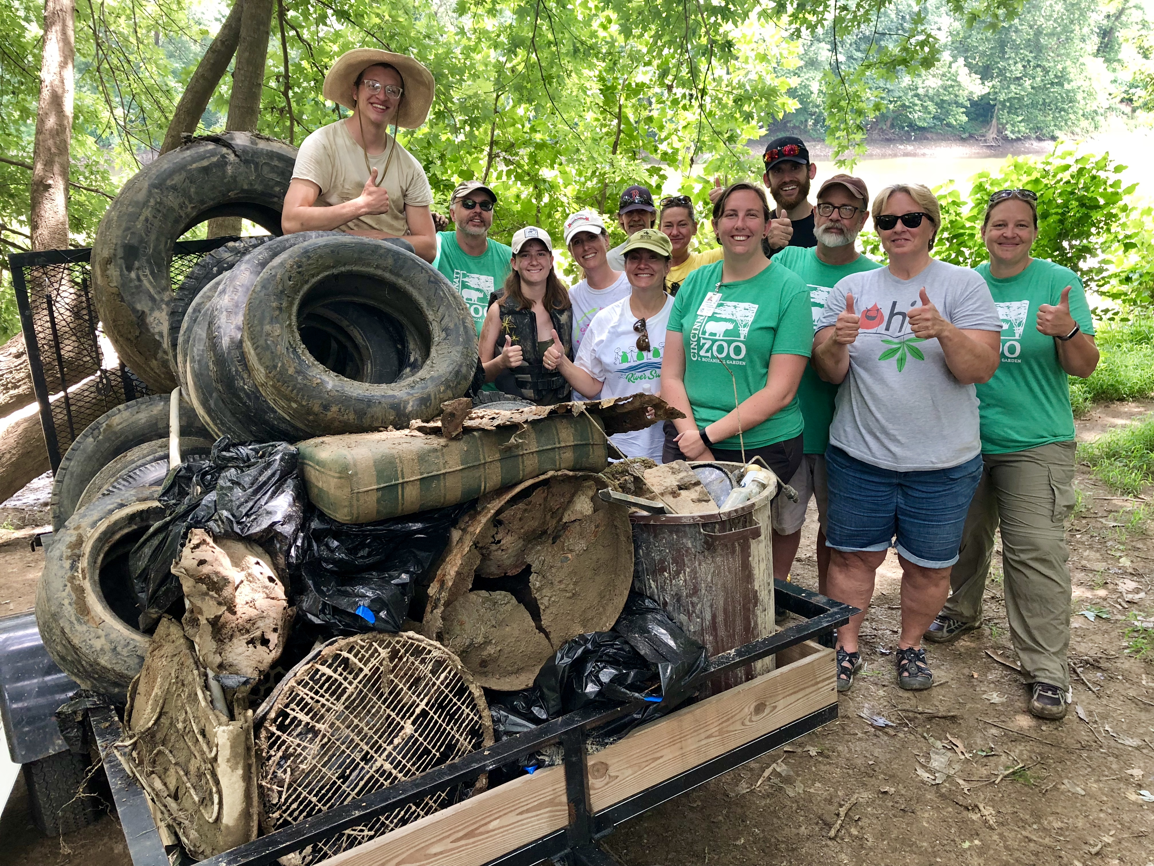 group of volunteers posing with trash they have collected