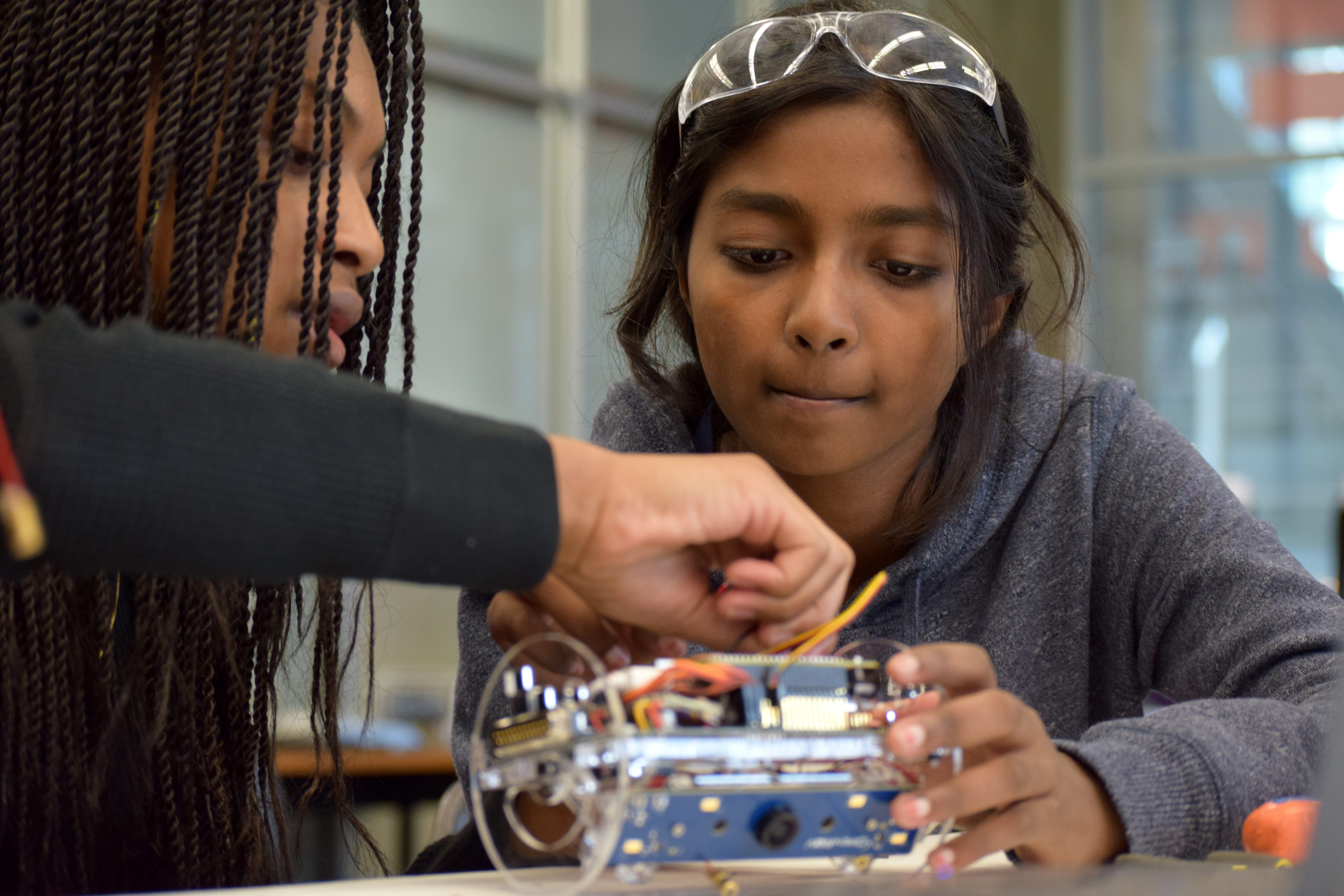 Two girls working on building a robot