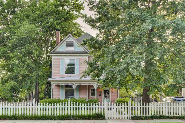 two story house with white picket fence
