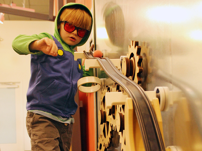 A child tinkering with the magnet wall