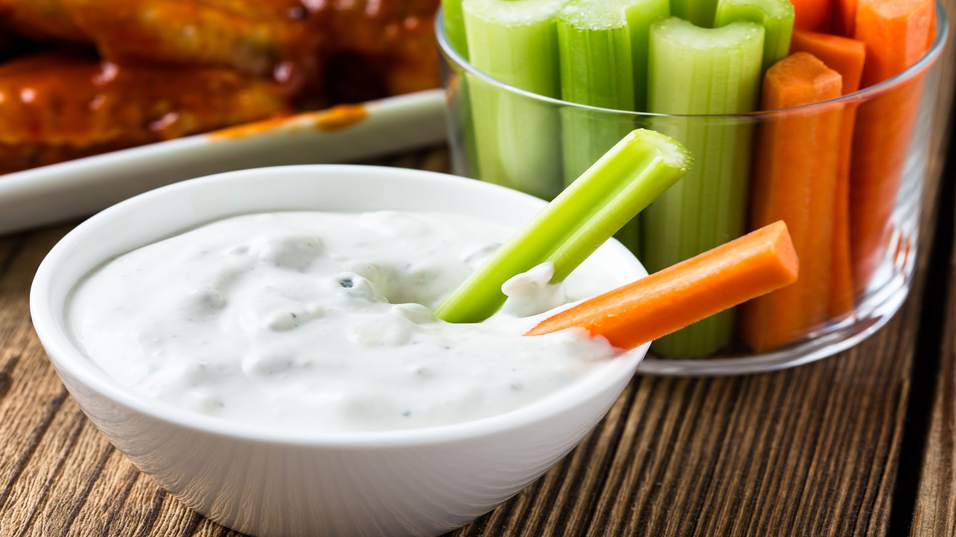 White bowl of blue cheese dressing with a carrot and celery stick sticking out and a clear bowl or celery and carrot sticks behind it. Behind that is a plate of bbq wings.