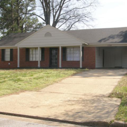 brown brick house with long driveway