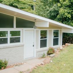 White slanted house with bird feeder