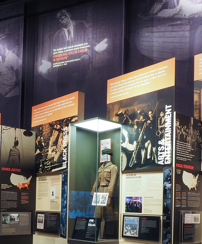 "Artifacts and Black-Face scrims in the museum exhibit ""I, Too, Am America: Combatting Jim Crow, 1896-1954"""