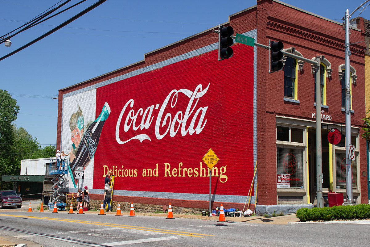 A large mural of a Coca Cola advertisement covers the side of a brick building.